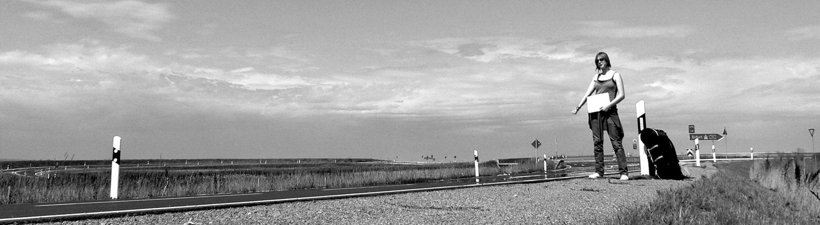 Schwarz-Weiß-Foto. Eine Tramperin steht am Straßenrand inmitten einer weiten Landschaft. Sie hält ihren rechten Arm ausgestreckt, in der linken Hand hält sie ein Schild. Neben ihr steht ein Rucksack.