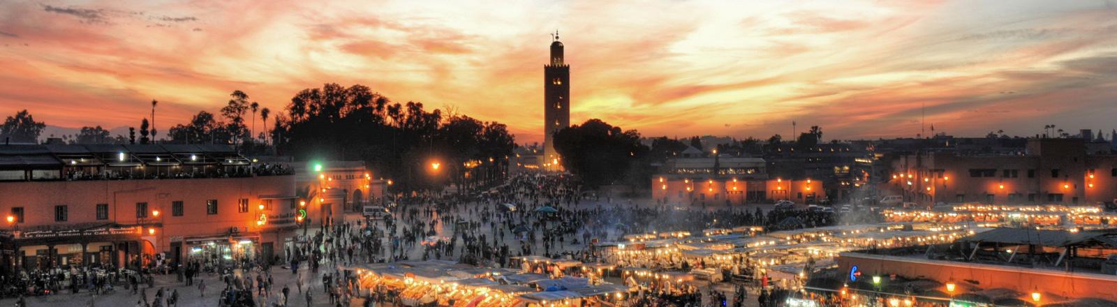 Eine Stadt in Marokko im rötlichen Abendlicht. Auf dem Marktplatz leuchten die Lichter der Verkaufsstände.