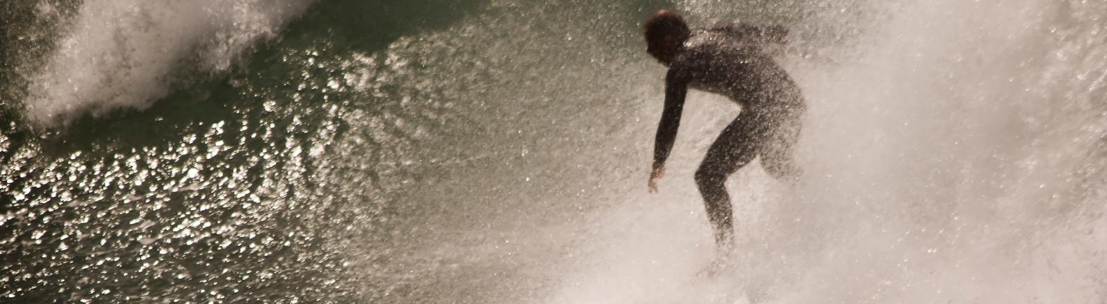 Ein Surfer reitet auf der Welle.