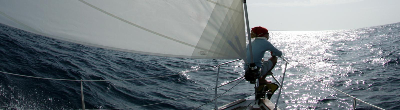 Ein Mann sitzt auf dem Bug eines Segelschiffs und blickt gegen den Horizont.
