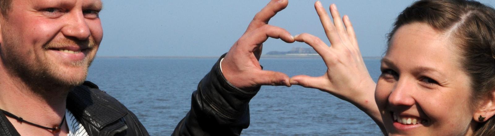 Holger Spreer und Nele Wree haben ihren Wohnsitz, die Hallig Süderoog (Schleswig-Holstein) mit ihren Fingern eingerahmt.