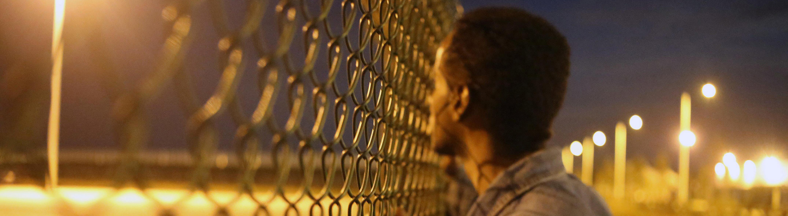 Ein Flüchtling steht vor dem Zaun in Calais, der die Flüchtlinge abhalten soll, auf die Fähre nach England zu gehen.