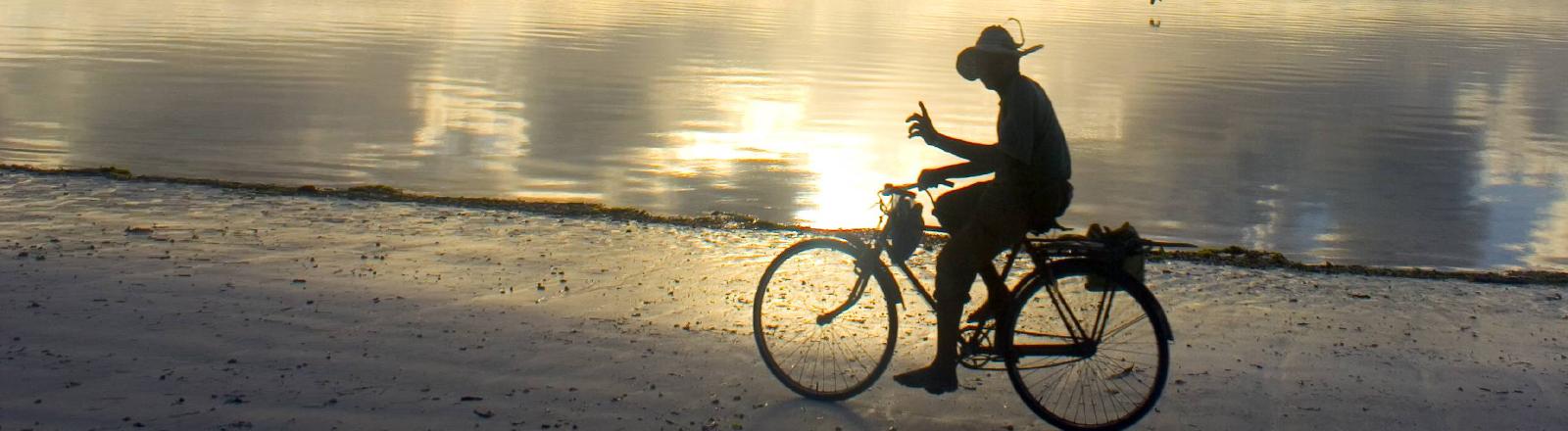Ein Mann fährt vor dem Sonnenuntergang Fahrrad.