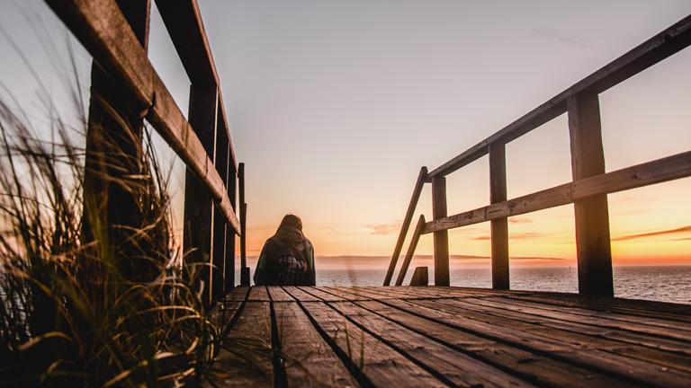 Frau sitzt auf einem Steg am Strand auf Sylt.