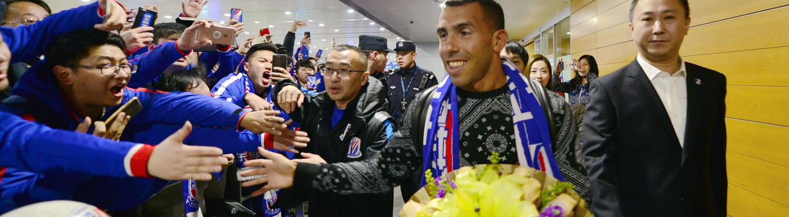 Der argentinische Fußballprofi Carlos Tevez wird von Fans am Flughafen in Schanghai am 17.01.2017 begrüßt.