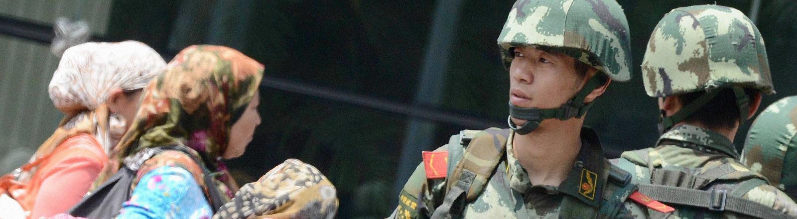 Uigurische Frauen und chinesische Soldaten.