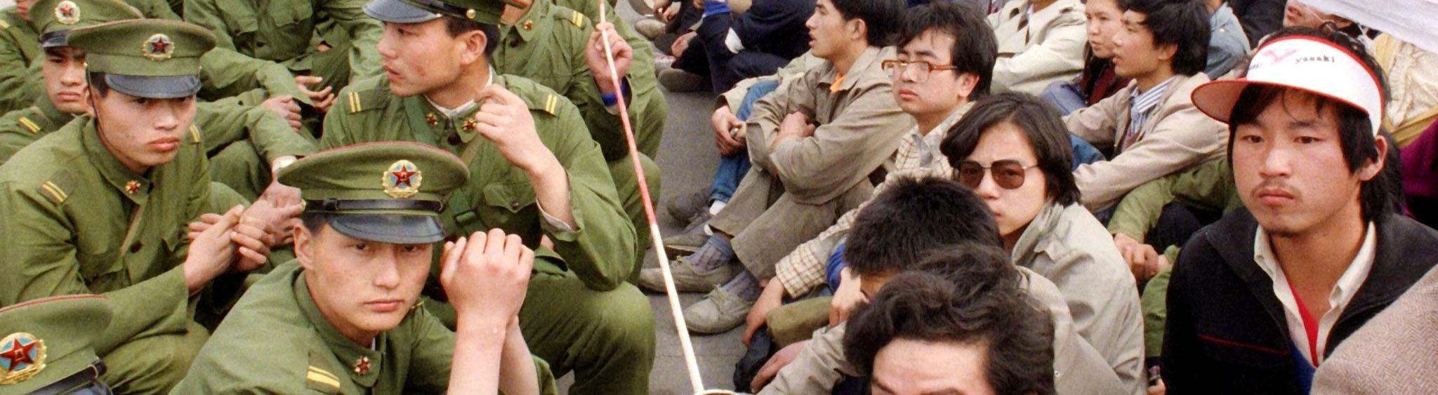 Einige hundert chinesische Studenten sitzen am 22.5.1989 vor der Großen Halle des Volkes in Peking einer Polizeieinheit gegenüber. Die Studenten hatten an einer nicht genehmigten Kundgebung anläßlich der Trauerfeier für den in Ungnade gefallenen Chef der Kommunistischen Partei Chinas, Hu Yaobang, teilgenommen. Am 4. Juni 1989 wurden die wochenlangen Proteste gegen Korruption und für mehr Demokratie durch den Einsatz von Militär blutig beendet. Bei dem grauenvollen Massaker am Platz des Himmlischen Friedens starben unzählige Menschen. Die genaue Zahl der Opfer bleibt unbekannt, soll aber um die eintausend betragen.