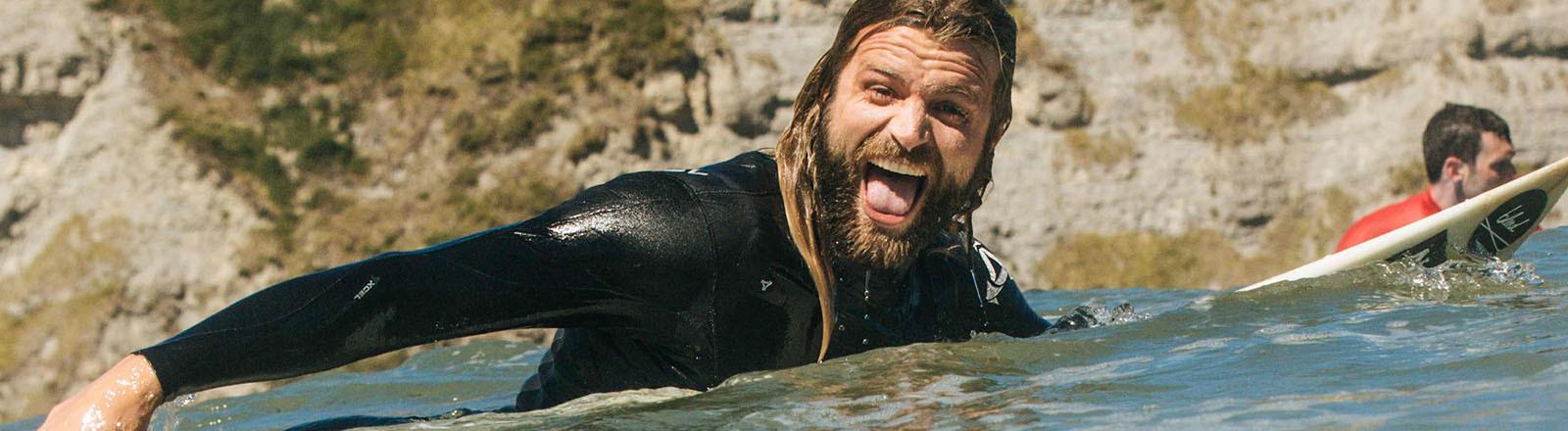 Carlo Drechsel auf seinem Surfbrett im Meer, dahinter Felsküste.