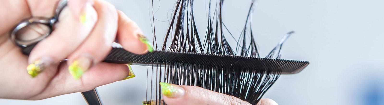 Einer Frau werden von einer Friseurin die Haare geschnitten.