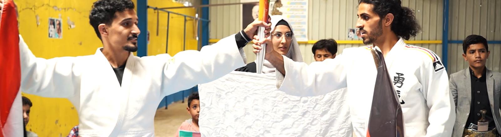 Der Judoka Shugga Nashwan steht neben seinem jementischen Judoka-Kollegen; sie halten gemeinsam eine olympische Fackel.
