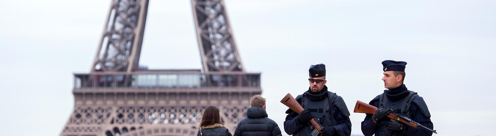 Passanten und bewaffnete Polizisten vor dem Eiffelturm.
