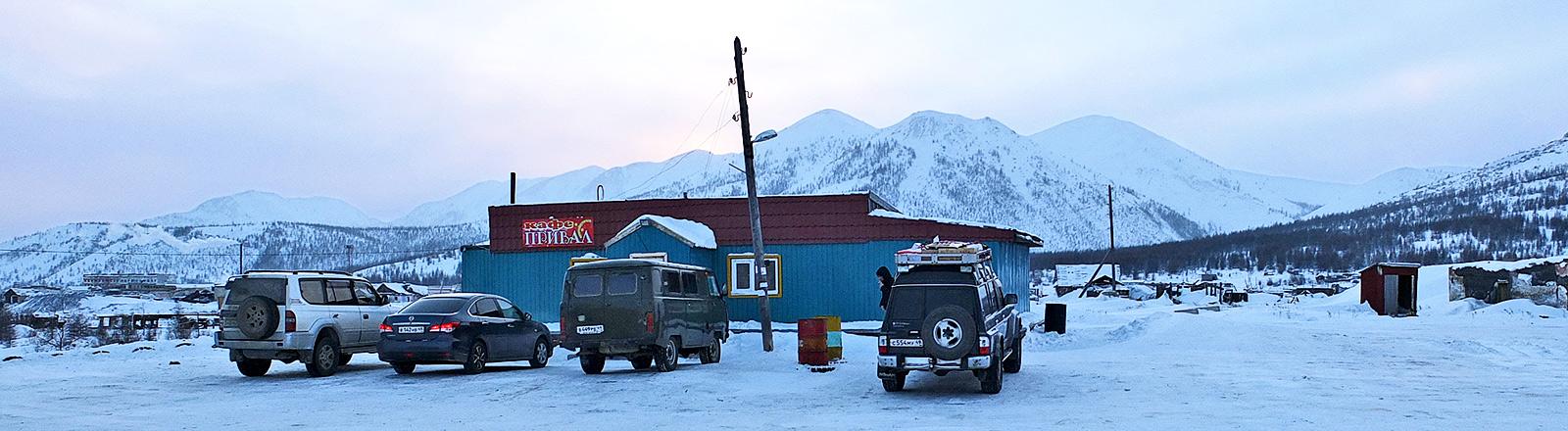Einige Autos stehen vor einer Hütte in einer verlassenen Schneelandschaft.