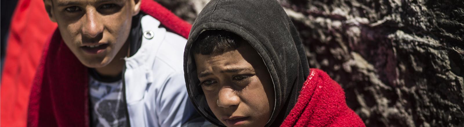 Zwei junge Flüchtlinge, in Decken gehüllt.