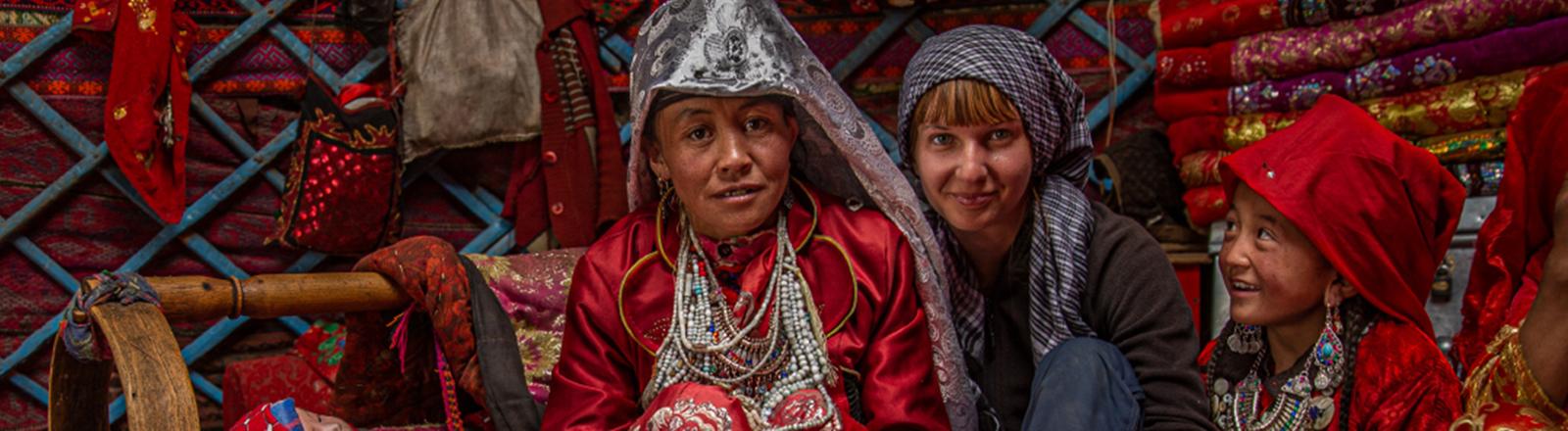 Die Fotografin Priska Seisenbacher mit einer Frau und einem Kind in einer Jurte in Pamir.