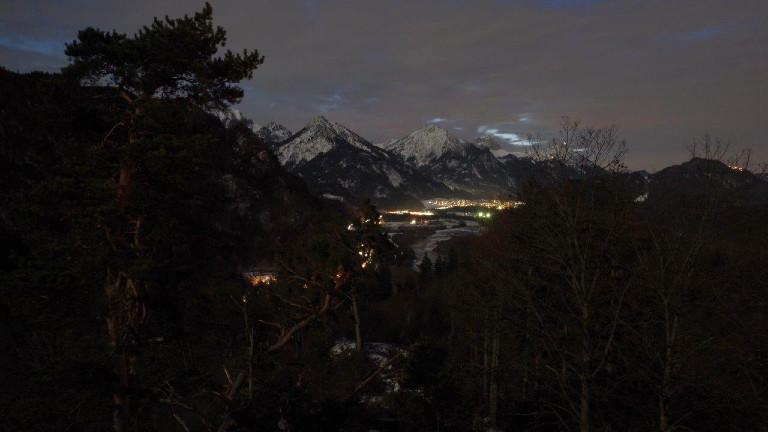 Blick durch die Wälder auf ein beleuchtetes Dorf bei Nacht