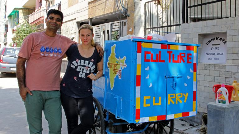 """Christina Franzisket und Nagender Chhikara vor einer Motorrikscha mit der Aufschrift """"Culture Curry"""""""