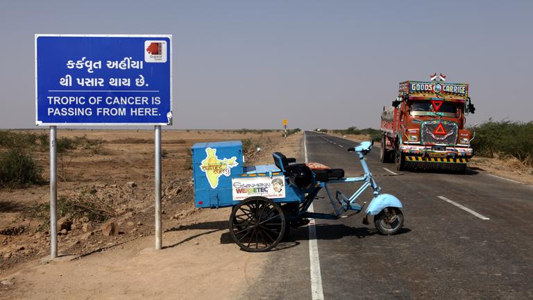 """Eine Motorrikscha mit der Aufschrift """"Culture Curry"""" steht vor einem Wegweiser mit indischer Schrift am Rand einer Landstraße, ein bunter Lkw fährt vorbei."""