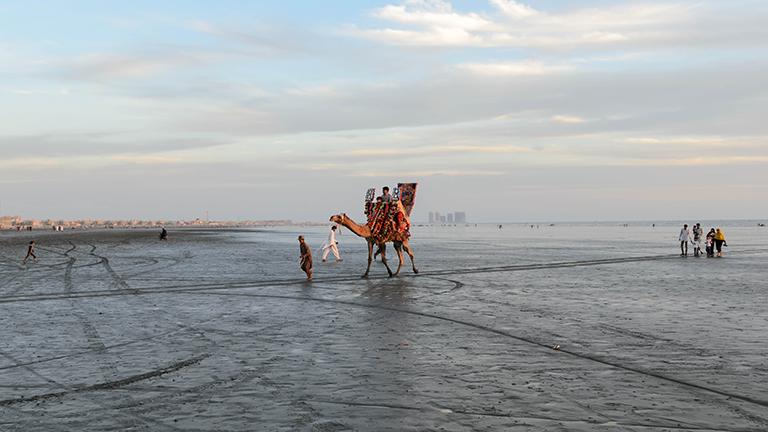 Ein Kamel mit Touristen auf weiter Flur.