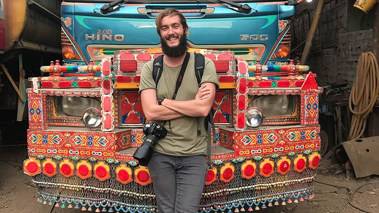 Clemens Sehi posiert vor einem bunten Bus in Pakistan.