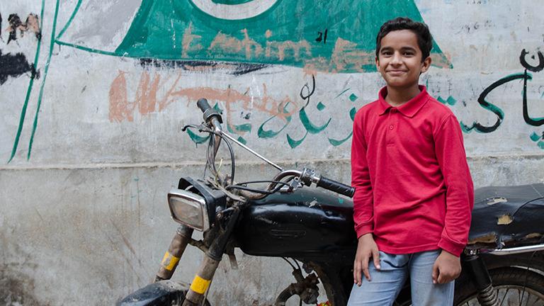 Ein Junge in einer Pakistanischen Straße posiert vor einem Motorrad.