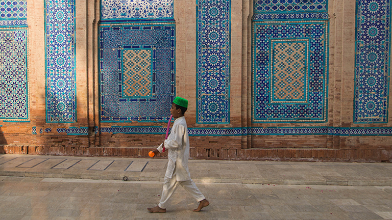 Ein Junge läuft durch eine pakistanische Altstadtgasse.