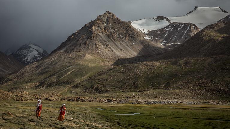 Zwei Frauen vor einer schroffen Berglandschaft in Pamir.
