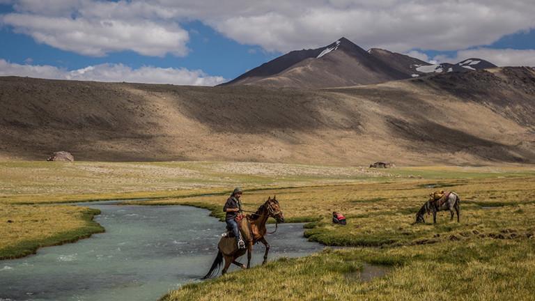 Die Fotografin und Autorin reitet auf einem Pferd im Pamir.