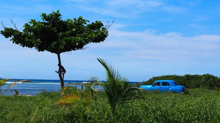 Idylle auf Kuba mit Meer und altem Auto