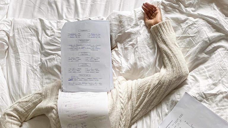 Sarah Richmond liegt auf dem Bett unter ihren Protugiesisch-Lernmaterialien begraben