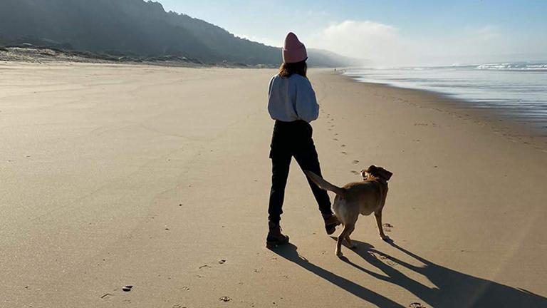 Sarah Richmond geht mit ihrem Hund an einem unberührten Strand spazieren.