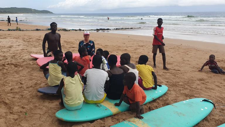 Ghanaische Surfschülerinnen und Surfschüler mit Angie Ringleb am Strand