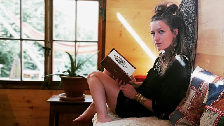 Geraldine Schüle sitzt in ihrem Zirkuswagen und liest ein Buch.