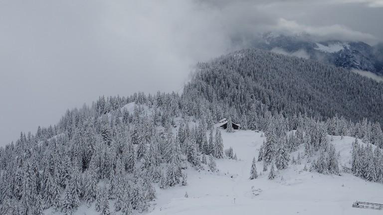 Blick auf die Blockhütte inmitten von schneebedeckten Tannen und Bergen im kosovarischen Hochland.