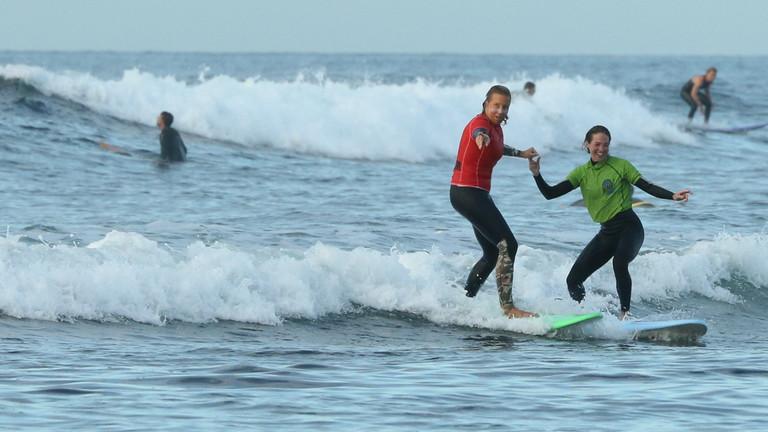 Angie Ringleb, Leiterin einer Surfschule auf Fuerteventura, mit Surfschülerin auf Brett