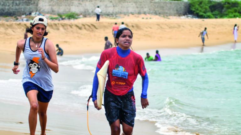 Zwei junge Surferinnen laufen am Strand entlang.