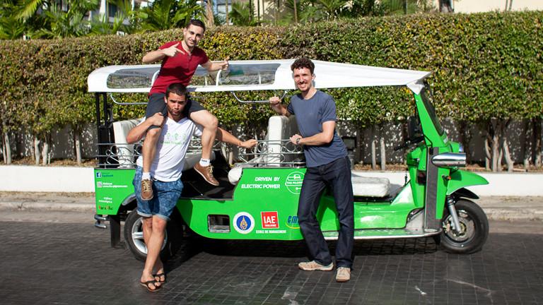 Drei Kungs vor einem grünen Tuk-Tuk