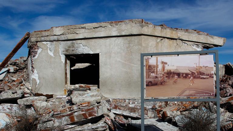 Ein verfallenes Haus. Im Vordergrund das Bild, wie es vor der Überflutung ausgesehen hat.