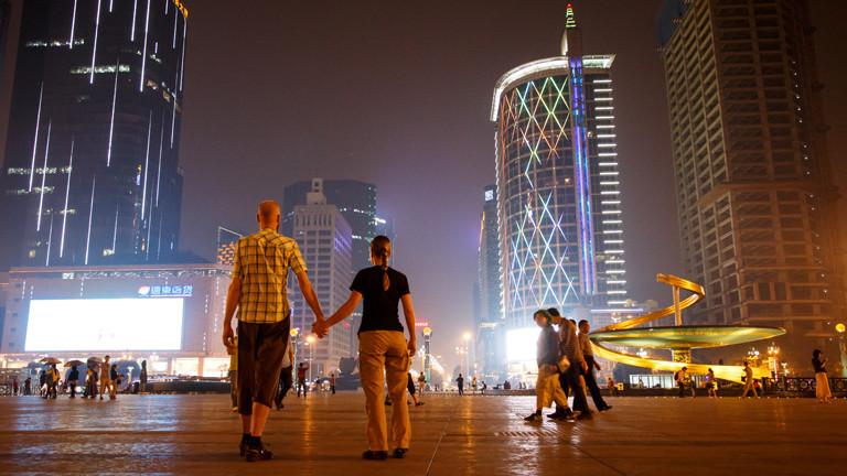 Paar hält sich an den Händen vor Hochhauskulisse in Asien.