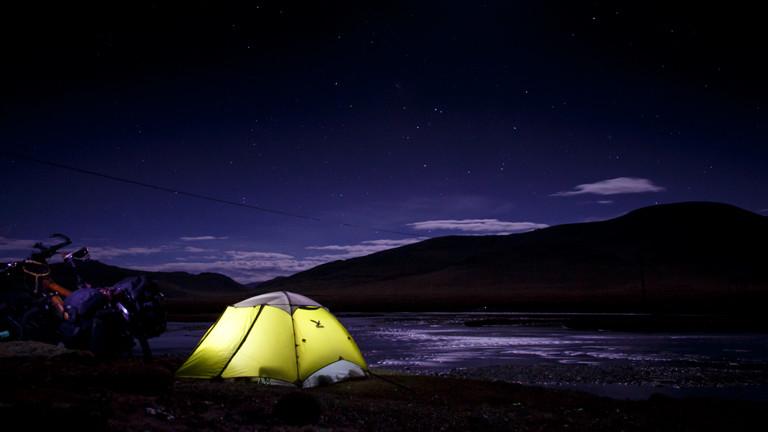 Leuchtendes Zelt vor Bergkulisse