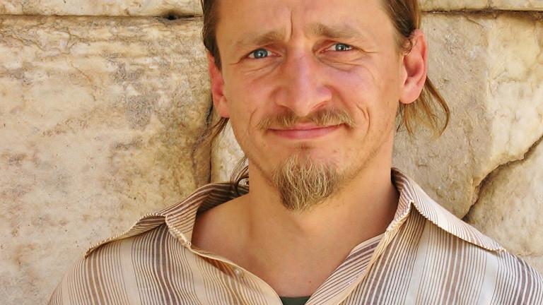Ein Foto von Oliver Lück. Er hat blond-braune Haare und ein Ziegenbärtchen.