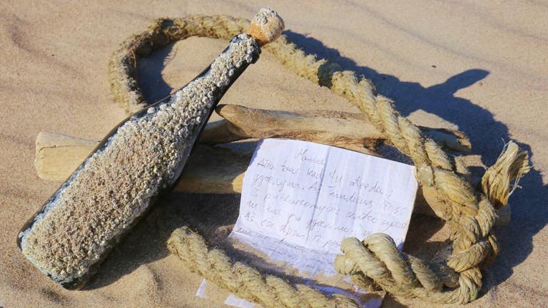 An Strand im Sand liegt ein Seil, darauf liegt ein Zettel und eine Flasche, die voller Sand und kleiner Muscheln ist.