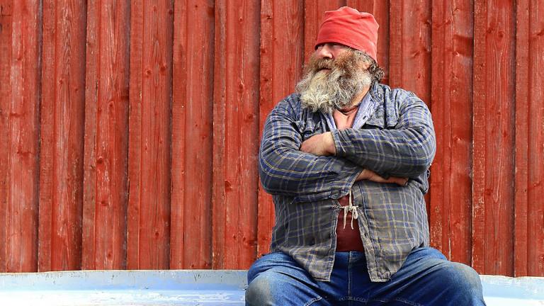 Ein Mann mit Bart sitzt auf einem umgedrehten Boot. Er trägt eine rote Mütze, Hemd und Hose.