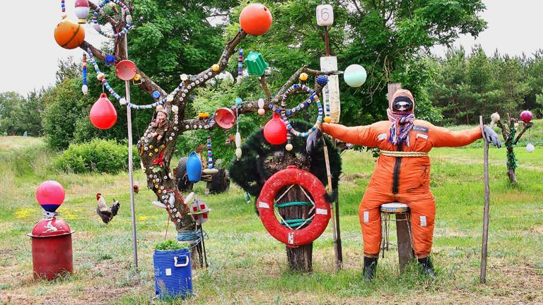 In einem Garten hängt Treibgut am Baum. Aus Treibgut ist auch ein Mann nachgebaut.