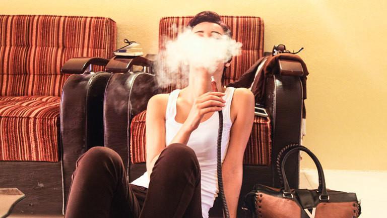 Eine Iranerin raucht Wasserpfeife, dabei trägt sie kein Kopftuch und ein Tanktop.
