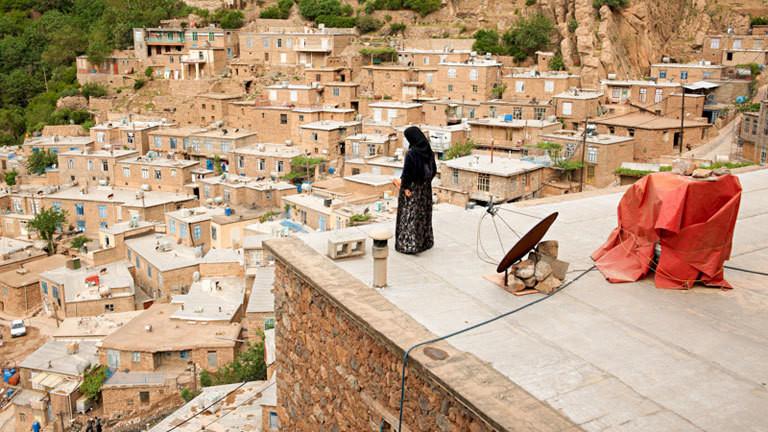 Eine Frau blickt von einem Dach auf eine Ortschaft hinunter.