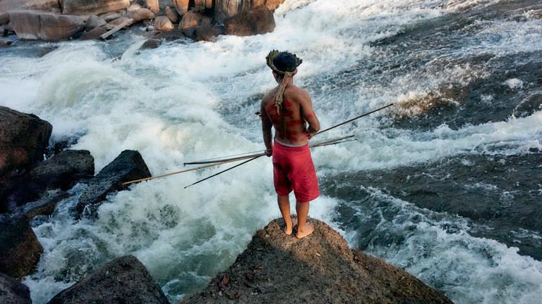 Tenharim-Krieger wartet auf Fische in einem Wasserfall.