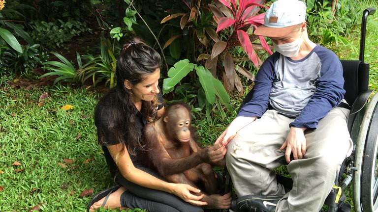 Der Orang-Utan Waise Boy gibt Benni Over die Hand.