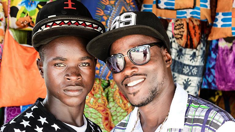 Zwei junge Männer stehen nebeneinander und lächeln, Ghana.