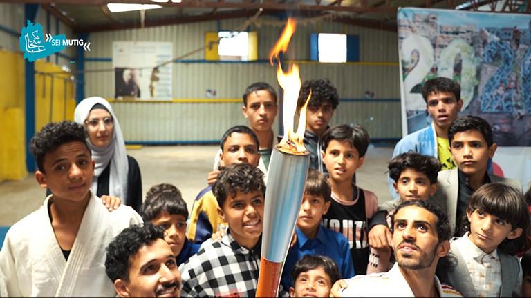 Der Judoka Shugaa Nashwan ist umringt von Kindern während der Mini-Spiele in Sanaa; jemand hält eine olympische Fackel ins Bild.