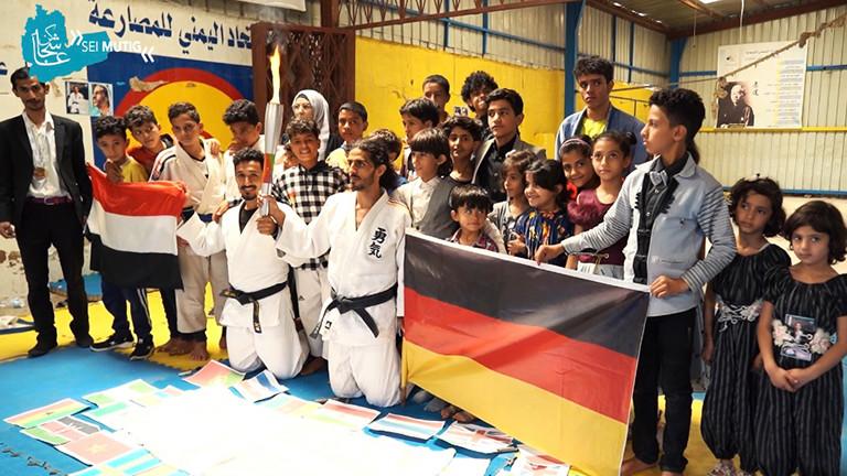 Shugga Nashwan und andere haben sich für ein Gruppenfoto während des Judo-Events in Sanaa aufgestellt. Er kniet, hinter ihm stehen viele Kinder. Die jemenitische und deutsche Flagge sind zu sehen.